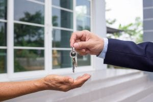 A person's handing over keys to rent out their property.